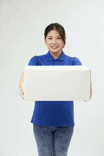 宅配を行う若い日本人女性の写真素材 [FYI04624609]