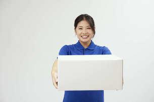 宅配を行う若い日本人女性の写真素材 [FYI04624610]