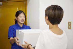 宅配を行う若い日本人女性の写真素材 [FYI04624612]