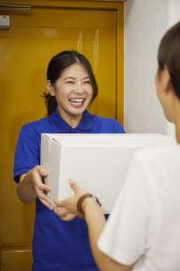 宅配を行う若い日本人女性の写真素材 [FYI04624613]