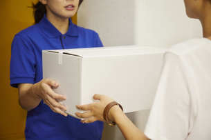 宅配を行う若い日本人女性の写真素材 [FYI04624614]