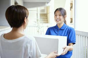 宅配を行う若い日本人女性の写真素材 [FYI04624615]