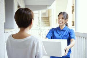 宅配を行う若い日本人女性の写真素材 [FYI04624616]
