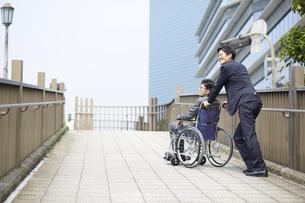 車椅子の男性を押しているスーツの男性の写真素材 [FYI04626210]