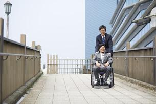 車椅子の男性を押しているスーツの男性の写真素材 [FYI04626211]