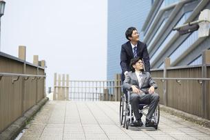 車椅子の男性を押しているスーツの男性の写真素材 [FYI04626212]
