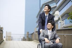 車椅子の男性を押しているスーツの男性の写真素材 [FYI04626213]
