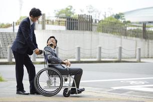 車椅子の男性を押しているスーツの男性の写真素材 [FYI04626214]