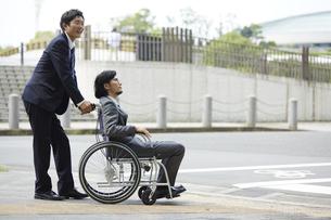 車椅子の男性を押しているスーツの男性の写真素材 [FYI04626215]