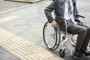 車椅子に乗るスーツ姿の男性と道路の写真素材 [FYI04626216]