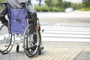車椅子に乗るスーツ姿の男性と道路の写真素材 [FYI04626217]