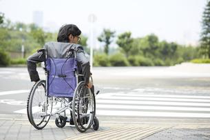車椅子に乗るスーツ姿の男性と道路の写真素材 [FYI04626218]