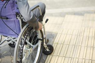 車椅子に乗るスーツ姿の男性と道路の写真素材 [FYI04626219]