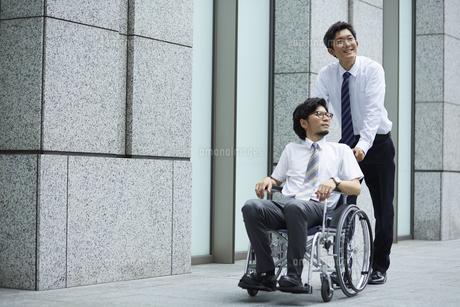 オフィス街で車椅子の男性を押しているスーツの男性の写真素材 [FYI04626220]