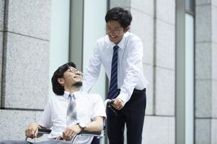オフィス街で車椅子の男性を押しているスーツの男性の写真素材 [FYI04626221]