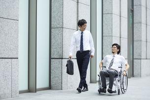 オフィス街で車椅子の男性と話すスーツの男性の写真素材 [FYI04626222]