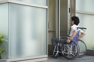 エレベーターに乗ろうとする車椅子の男性の写真素材 [FYI04626223]