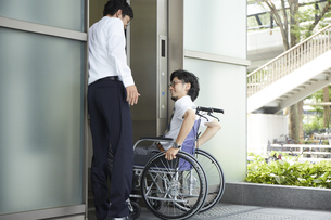 エレベーターに乗ろうとする車椅子の男性と助ける男性の写真素材 [FYI04626224]