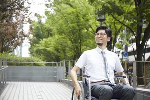 スロープを笑顔で通行する車椅子の男性の写真素材 [FYI04626225]