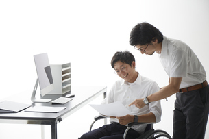 車椅子で働く男性と話す男性の写真素材 [FYI04626228]
