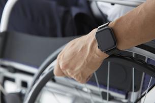 車椅子の男性のスマートウォッチのアップの写真素材 [FYI04626229]