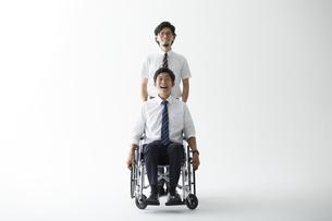 スーツを着て車椅子に乗る男性と立つ男性の写真素材 [FYI04626230]
