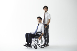 スーツを着て車椅子に乗る男性と立つ男性の写真素材 [FYI04626231]