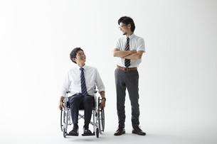 スーツを着て車椅子に乗る男性と立つ男性の写真素材 [FYI04626233]