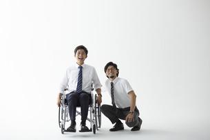 スーツを着て車椅子に乗る男性と寄り添う男性の写真素材 [FYI04626234]