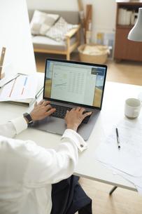 部屋の一角のデスクでノートパソコンに向かって作業する女性の手元の写真素材 [FYI04626235]