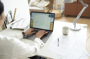 部屋の一角のデスクでノートパソコンに向かって作業する女性の後ろ姿の写真素材 [FYI04626238]