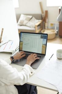 デスクでノートパソコンに向かって作業する女性の手元の写真素材 [FYI04626240]