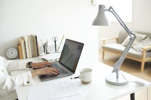 デスクでノートパソコンに向かって作業する女性の手元の写真素材 [FYI04626241]
