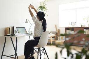 部屋の一角にあるワークスベースで伸びをして休憩する女性の後ろ姿の写真素材 [FYI04626244]