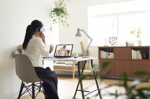 デスクでノートパソコンに向かってヘットセットを着けてオンライン会議をする女性の後ろ姿の写真素材 [FYI04626247]