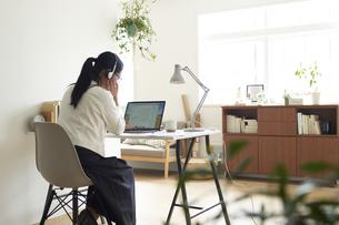 デスクでノートパソコンに向かってヘットセットを着けてオンライン会議をする女性の後ろ姿の写真素材 [FYI04626250]