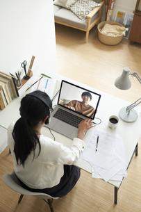 デスクでノートパソコンに向かって作業する女性の後ろ姿の写真素材 [FYI04626251]