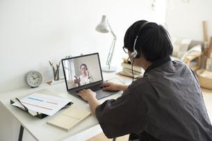 部屋の一角のワークスペースでノートパソコンを前にヘッドセットを付けて作業する男性の後ろ姿の写真素材 [FYI04626268]