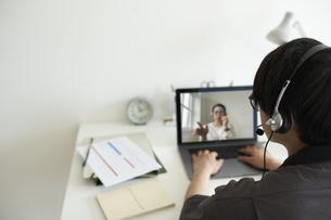部屋の一角のワークスペースでノートパソコンを前にヘッドセットを付けて作業する男性の後ろ姿の写真素材 [FYI04626270]