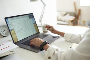 部屋の一角のワークスペースでノートパソコンを前に作業する女性の手元の写真素材 [FYI04626284]