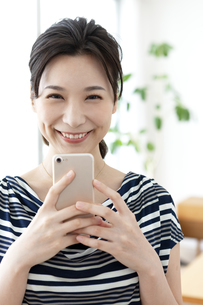 スマートフォンを持つ笑顔の女性の写真素材 [FYI04626328]