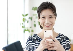 スマートフォンを持つ笑顔の女性の写真素材 [FYI04626329]