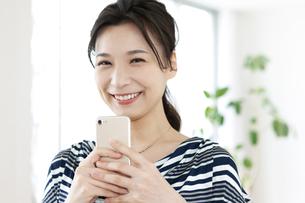 スマートフォンを持つ笑顔の女性の写真素材 [FYI04626330]