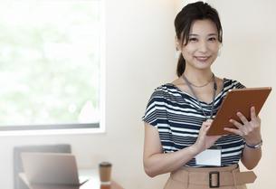タブレットPCを持つビジネスウーマンの写真素材 [FYI04626335]