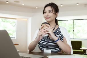 コーヒーカップを持っているビジネスウーマンの写真素材 [FYI04626339]