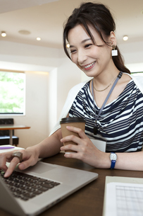 コーヒーを飲みながら仕事をするビジネスウーマンの写真素材 [FYI04626345]