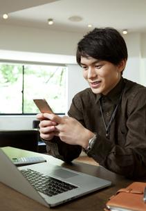 スマートフォンを操作するビジネスマンの写真素材 [FYI04626381]