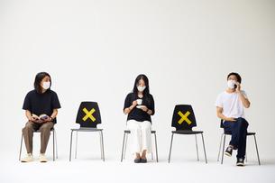横一列に並んだ椅子に座るマスクをした男性二人と女性一人の写真素材 [FYI04626403]