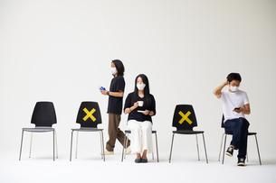 横一列に並んだ椅子に座るマスクをした男性一人と女性一人に歩く男性一人の写真素材 [FYI04626404]