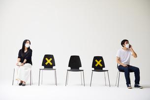 横一列に並んだ椅子に座るマスクをした男性一人と女性一人の写真素材 [FYI04626405]